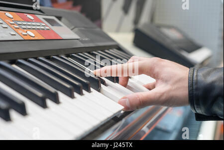 piano keyboard synthesizer with hand - Stock Photo