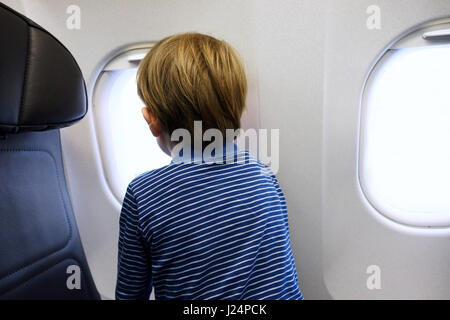 Little boy looking out of aeroplane window - Stock Photo