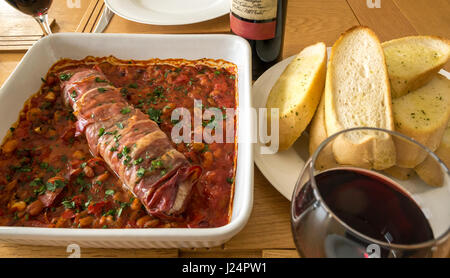 Close up Italian pork tenderloin on bed of tomatoes, beans and garlic with plate of garlic bread, glass of red wine, - Stock Photo