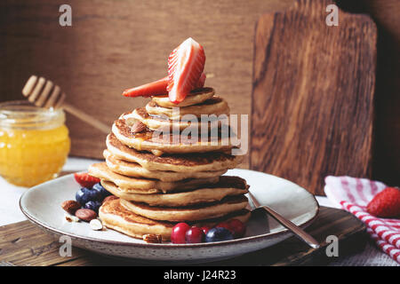 Healthy spelt whole grain pancakes with honey, strawberries, blueberries and nuts on a plate. Toned image, closeup - Stock Photo