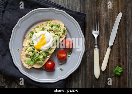 Healthy breakfast toast: poached egg, mashed avocado with cilantro and lime juice, sunflower seeds and cherry tomatoes - Stock Photo