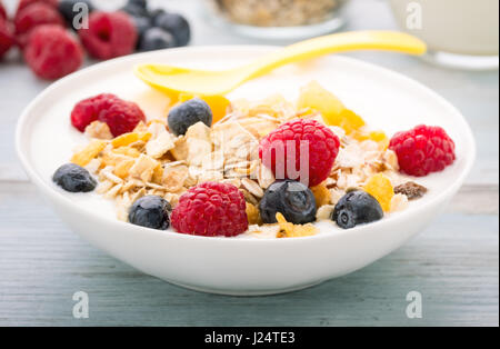 Cereals and cornflakes with raisins and fresh berries. - Stock Photo