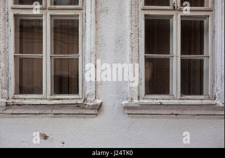 Exterior of an old house, two wooden windows and vintage curtains. - Stock Photo