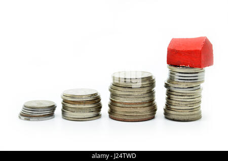 Coins stacked up in piles with color house. Saving for home concept - Stock Photo