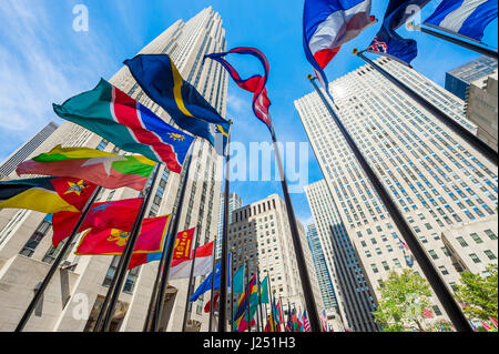 NEW YORK CITY - SEPTEMBER 2, 2016: International flags fly at the foot of the Art Deco skyscrapers at Rockefeller - Stock Photo