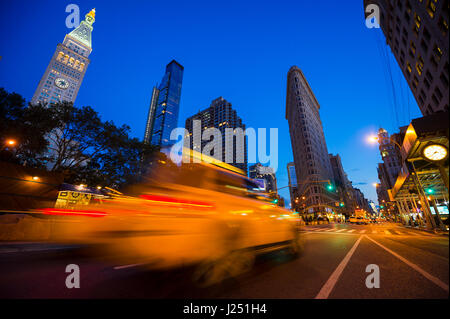 Traffic passing in motion blur in a bright evening view of the streets of New York City at Madison Square, where - Stock Photo