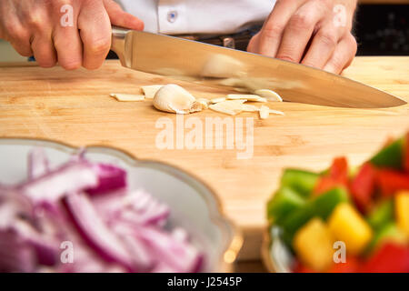 Man's hands cutting fresh garlic in the kitchen, preparing a meal for lunch. Paprika and onions in the foreground. - Stock Photo