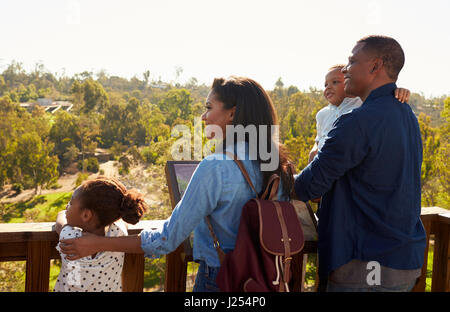 Family Standing On Outdoor Observation Deck Looking At View - Stock Photo