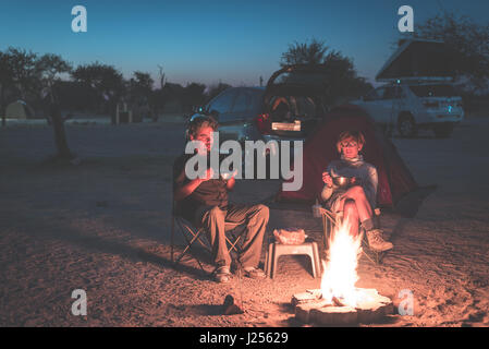 Adult couple relaxing in camping site by night. Adventure in National Park, South Africa. Burning camp fire and - Stock Photo