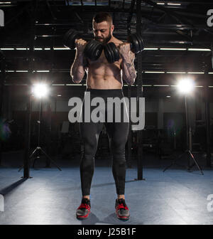 Muscular  shirtless bodybuilder guy doing exercises with dumbbells in the modern fitness center - Stock Photo