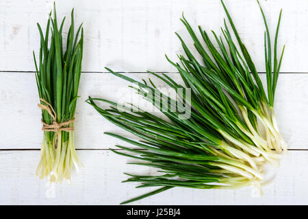 Young feathers (leaves) of a green onion on a white wooden background, collected in a bundle and scattered. The - Stock Photo
