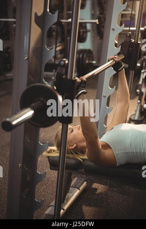 Fit woman exercising with smith machine in the gym - Stock Photo