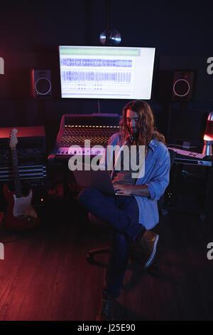 Male audio engineers using laptop in recording studio - Stock Photo