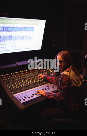 Portrait of female audio engineer using sound mixer in recording studio - Stock Photo