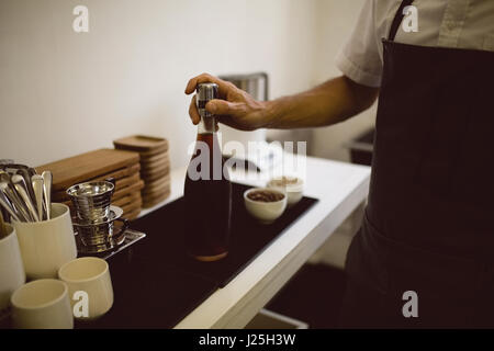 Male barista holding bottle full of black coffee in coffee shop - Stock Photo