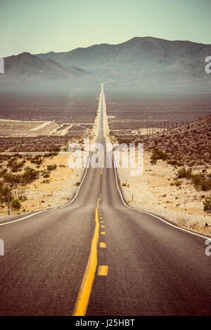 Classic panorama view of an endless straight road running through the barren scenery of the American Southwest in - Stock Photo