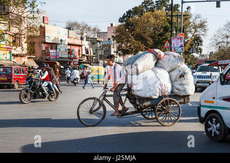 Local Indian man pedalling a tricycle carrying a large heavy load of sacks at a road junction in a busy street in - Stock Photo