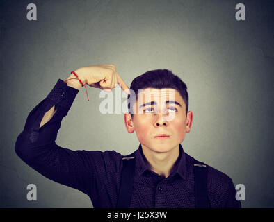 Closeup portrait man scratching head, thinking about something, looking up, isolated on gray wall background. Human - Stock Photo