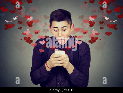 Portrait young handsome shocked man sending receiving love sms text message on mobile phone with red hearts flying - Stock Photo