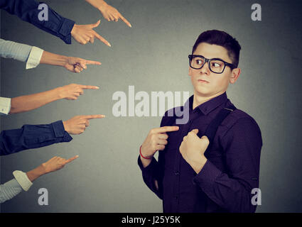 Blaming you. Anxious man judged by different people pointing fingers hands at him. Concept of accusation of guilty - Stock Photo