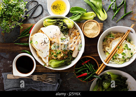 Asian food concept with fried rice, baby bok choy, eggs and soy sauce - Stock Photo