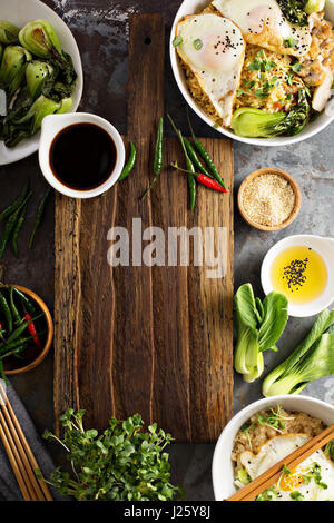 Asian food concept with fried rice, baby bok choy, eggs and soy sauce with copyspace - Stock Photo