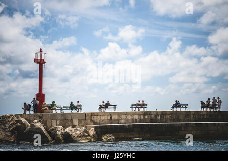 People Sitting on Benches, Dubrovnik Harbor, Croatia - Stock Photo