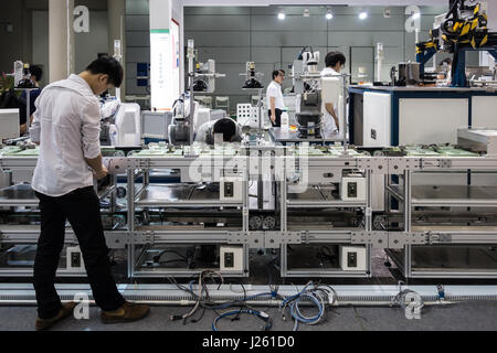 Chinese workers setting up (or disassembling) assembly line in Shenzhen, China - Stock Photo