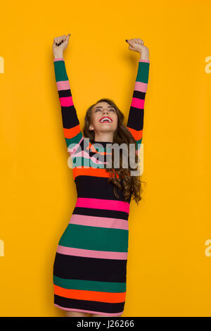 Happy beautiful young woman in colorful vibrant striped dress with long sleeves is holding arms raised, smiling - Stock Photo