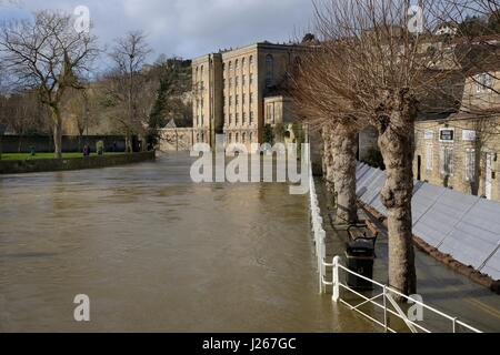 River Avon in spate through Bradford-on-Avon, with emergency flood defences to protect buildings from flooding, - Stock Photo