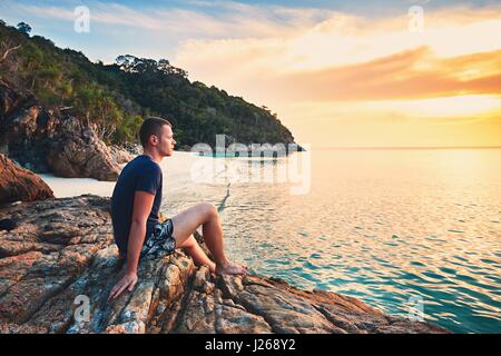 Contemplation at the sunset. Alone young man on the beautiful sand beach. - Stock Photo