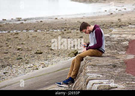 Man sitting on ledge using his mobile phone.Seaside in Background.Beaumaris beach,Anglesey,North Wales,Uk.21 April,2017. - Stock Photo