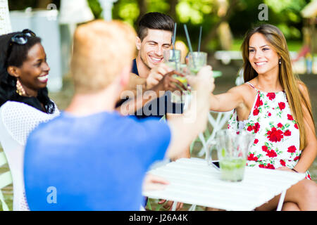 Group of cheerful happy people toasting while sitting at a table outdoors on a hot summer day - Stock Photo