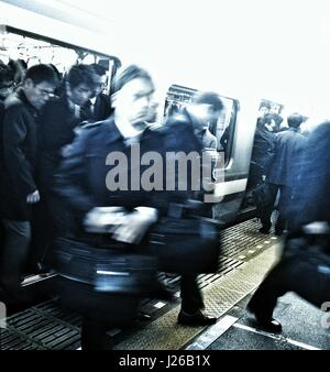 Commuters getting off train, Tokyo, Japan - Stock Photo