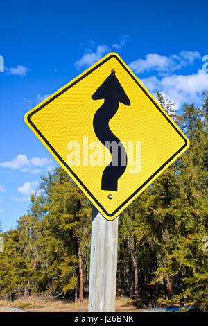 Warning of curvy road ahead - Stock Photo