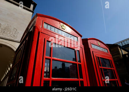 Low angle shot of two red telephone boxes against the blue sky in London, England, UK - Stock Photo