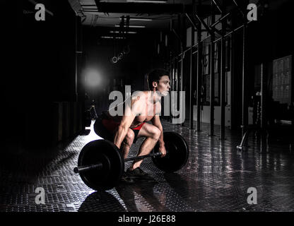 Muscular man doing the crossfit exercise in the gym.Preparing to - Stock Photo