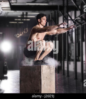 Fit young man box jumping at a crossfit gym.Athlete is performin - Stock Photo