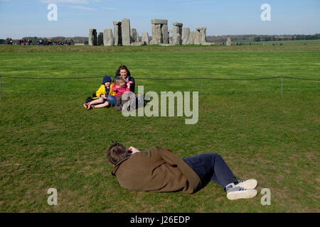 Family taking pictures in front of the Stonehenge prehistoric monument in Wiltshire, England - Stock Photo