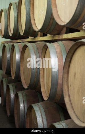 Oak wood aging barrels in a winery storeroom - Stock Photo