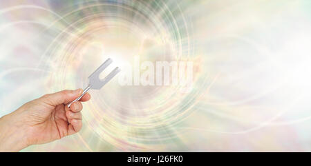 If you could see the sound waves made by an Angel Tuning Fork - female hand holding a short tuning fork on an angelic - Stock Photo