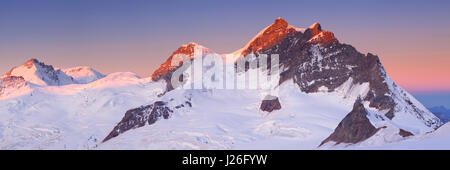 Sunrise over the Jungfrau peak from Jungfraujoch in Switzerland on a clear morning. - Stock Photo