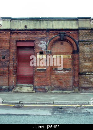 ... abandoned building with red shutters and bricked up doorway - Stock Photo