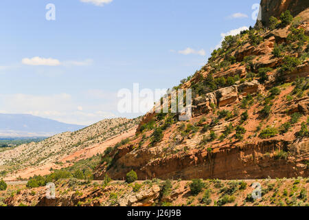 Part of the Rim Rock Drive, the road going through the Colorado National Monument, with part of the Grand Mesa in - Stock Photo