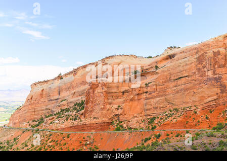 Cars driving on the Rim Rock Drive, the road going through the Colorado National Monument, in front of a red cliff. - Stock Photo