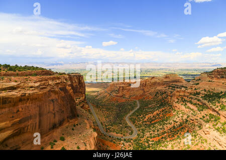 Cars driving on the Rim Rock Drive in the Fruita Canyon as part of the Colorado National Monument with the Book - Stock Photo