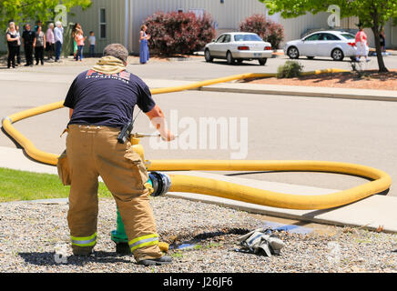 Grand Junction, USA - May 28, 2016: Fireman in action connecting a fire hose to a hydrant. In the back bystanders - Stock Photo