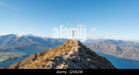 Hiker cutting a caper, View of mountains and lake, Roys Peak, Lake Wanaka, Southern Alps, Otago Region, Southland, - Stock Photo