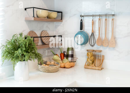 Kitchen wood utensils, chef accessories. Hanging copper kitchen with white tiles wall. - Stock Photo