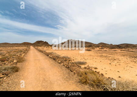 The Isla de Lobos in Fuerteventura, Spain with a road through the typical moon like volcanic landscape of the island. - Stock Photo